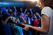 holidays, music, nightlife and people concept - close up of singer playing electric guitar and singing on stage over happy fans crowd waving hands at concert in night club poster
