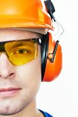 Close-up face portrait of young builder worker in protective hardhat with ear muff and protective glasses poster
