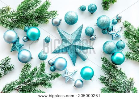Toys for christmas tree. Blue stars and balls near pine branches on white background top view