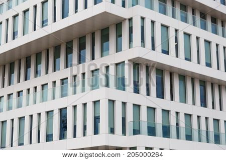 Texture of the modern facade. Perspective view of a white concrete facade with blue windows.