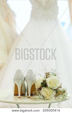 Wedding shoes and flowers on a table and wedding dress