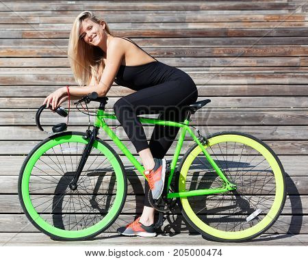 Fitness princess with long hair blond girl in black skin-tight sexy outfit and sneakers sitting on a green fashion fix bike. Outdoor.