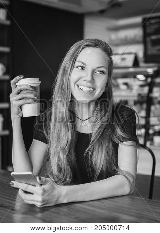 Beautiful woman laughing holding a cup of coffee and a cell phone black and white
