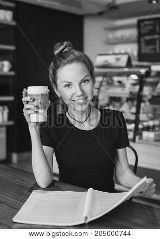 Portrait of a beautiful woman with a copybook and a cup of coffee looking at camera. Student preparing for the exams. black and white