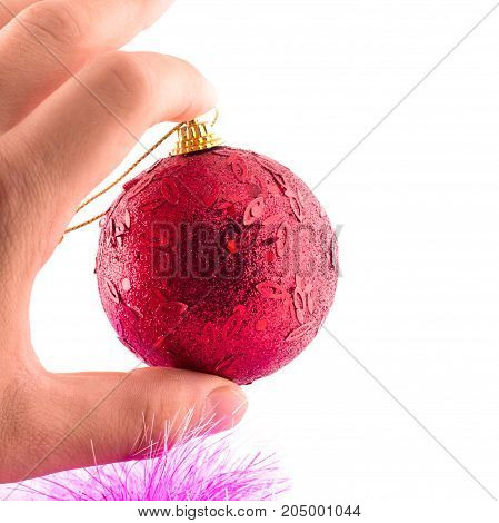 bright red christmas ball between two fingers fingers on a white background