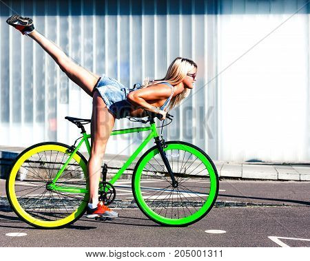 Beautiful blonde girl doing tricks and having fun on the steep green fixed bicycle in the city park of Europe. Outdoor.