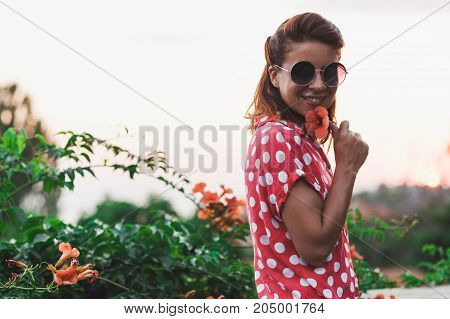 Young woman smelling flower in the garden enjoying sunset