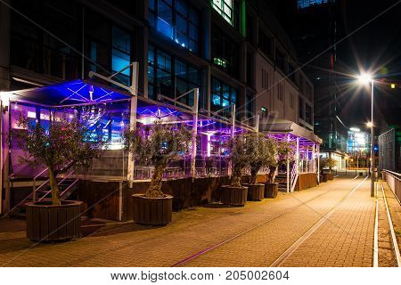 Outdoor cafe on city street near road with tram ways at night with neon illumination
