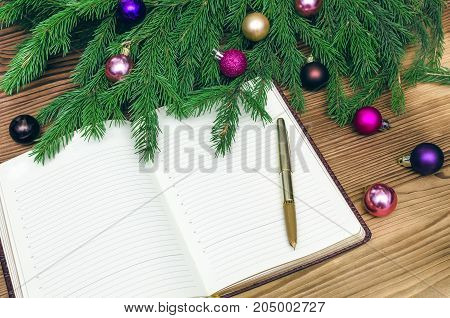 Open book with blank empty pages in Christmas tree branches with christmas balls around on burnt wooden board background. Text new year greetings.