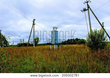 An electric transformer standing in the middle of the field.