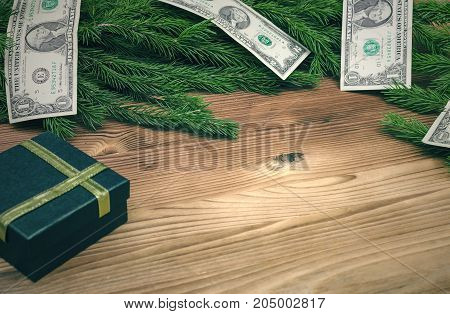 Present box and money banknotes in Christmas fir tree branches on burnt wooden board surface background with copy space. Christmas decorations.