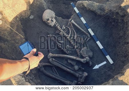 Archaeological excavations and finds (bones of a skeleton in a human burial) working tool ruler knife brush a detail of ancient research prehistory. Archaeologist photographs ancient burial rights
