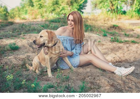 Girl on nature with a dog on sand