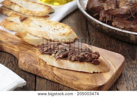 Toast with stewed beef. Peposo served over bruschetta. Italian Cuisine.