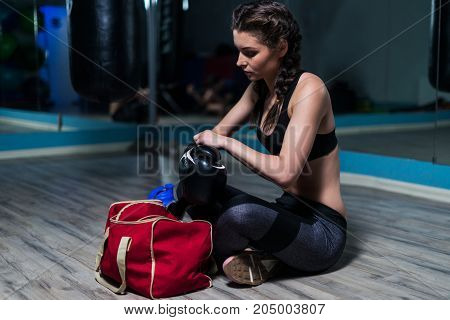 Young fighter boxer girl wearing boxing gloves before  training. She is sitting in gym