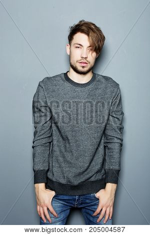 Handsome young man in smart casual wear looking at camera  while standing against grey background