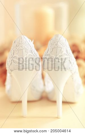 White lace wedding shoes on a orange background