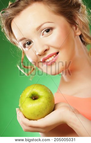 blond happy woman eat green apple over green background