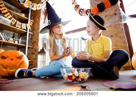 Sweets For Us! Treat Or Trick! Friendly Small Kids In Carnival Head Wear, With Colorful Treats, Near