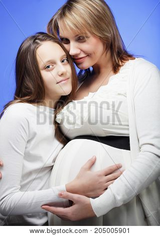 pregnancy, motherhood, people and family concept - happy pregnant woman with eldest daughter, studio shot