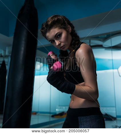 Young fighter boxer girl with hand bandage in training with pink dumbbells. Woman power and beauty