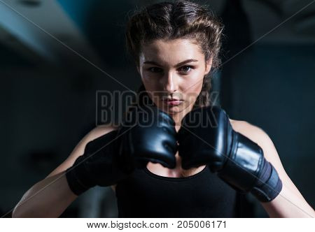 Young fighter boxer girl wearing boxing gloves before  training. She is looking at camera