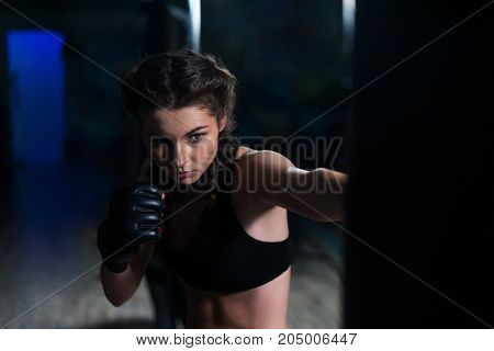 Young fighter boxer fit girl wearing boxing gloves in training with heavy punching bag in gym. Moment before punch. Woman power