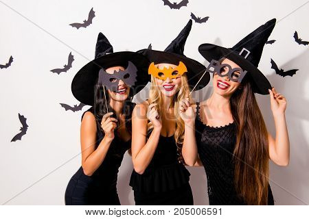 Group Of Three Diverse Charming Coquettes In Dark Masquerade Elegant Dresses, Masks On Eyes, Smiling