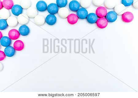 Top left frame of colored chocolate coated candy. Isolated on white background. Copy space