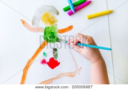 The child is drawing with a brush with acrylic paints on a blank sheet of white paper. Blurred