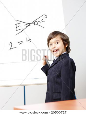 Genius little boy writting E=mc2 on the board, new formula instead, conceptual idea