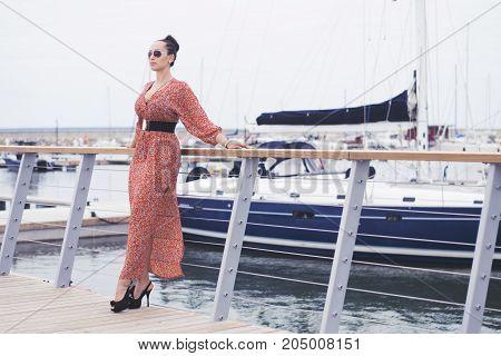 fashionable brunette woman wearing long red dress in sunglasses taking a walk near sea, pier with yachts