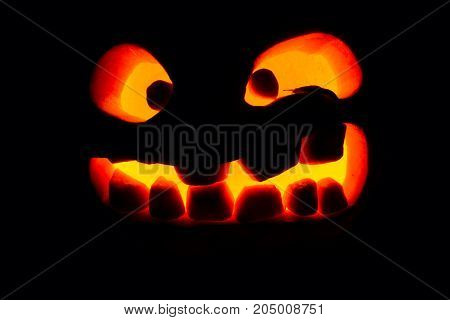 Halloween Concept. An Ominous Pumpkin Isolated In The Dark, With An Orange Warm Glow From The Inside