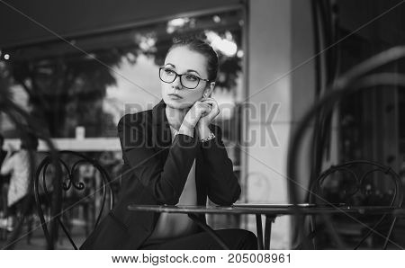 Sad business woman in suit with glasses sitting in the cafe black and white
