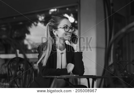 Young business woman or student in suit talking on the phone and smiling