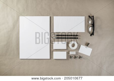 Photo of blank stationery set on craft paper background. Corporate ID template. Responsive design mockup. Top view.