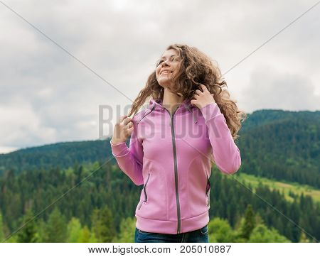 Curly young woman enjoying the view in the top of mountain on a hot summer day. Lifestyle concept