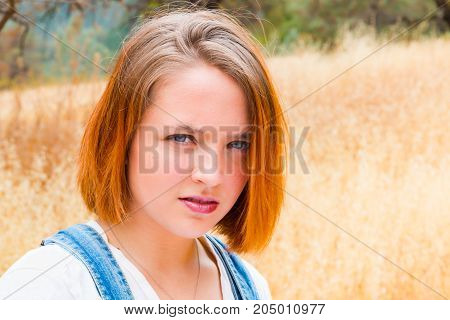 Beautiful Face of Girl With Read Hair Standing in Field