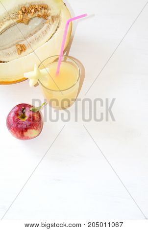 cut the melon next to the red Apple, a glass of smoothie with a slice of melon with a straw near all on wooden white background