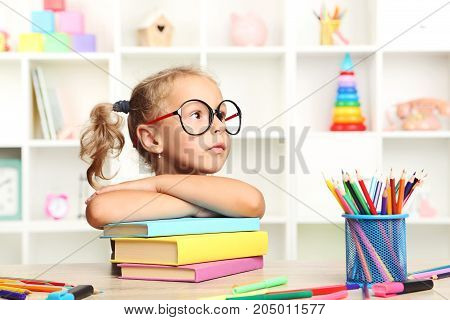 Little Girl Sitting With Books At The Table