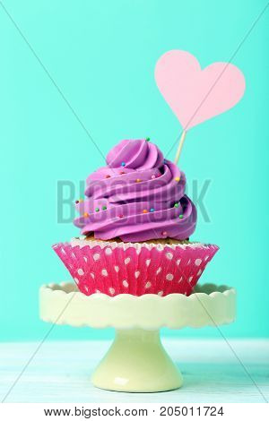 Tasty and sweet cupcake on a green background