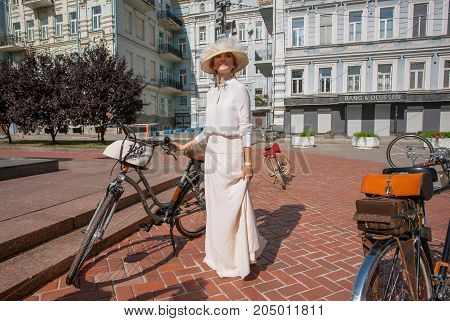 KYIV, UKRAINE - SEP 17, 2017: Beautiful woman in white vintage clothing ready for cycling on old bicycle at fashion festival Retro Cruise on June 17, 2017. Kiev is the 8th most populous city in Europe