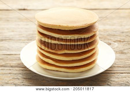 Tasty Pancakes In Plate On Wooden Table