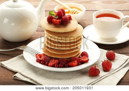 Tasty Pancakes With Berries And Cup Of Tea On Wooden Table