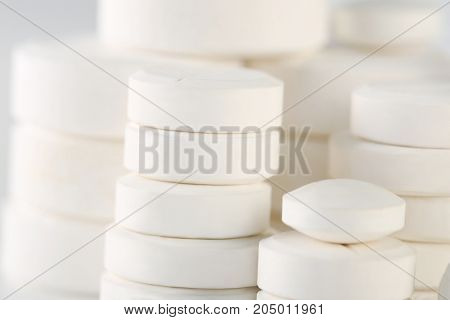 Heap of white pills background, close up