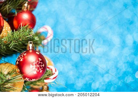 Christmas tree with balls and candies on blue glitter background. Happy New Year and Xmas concept