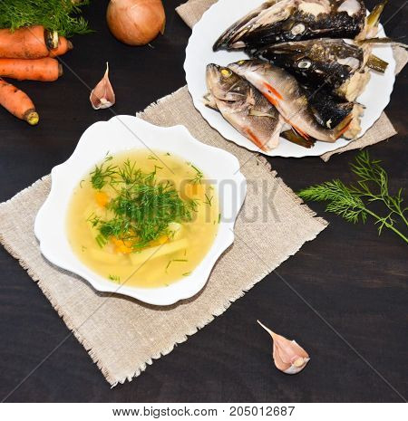 fish soup ear in a white plate next to the plate of the head slaves and small fish and next to the carrots and greens on a black background