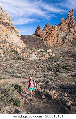 Happy girl hiker walking on mountain path. Inspire and motivate concept outdoors activity. Female runner or climber looking at inspirational landscape on rocky trail on Tenerife Canary Islands