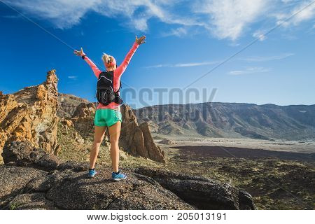 Hiking or climbing success with arms raised concept. Female runner or hiker celebrating on mountain top in inspirational landscape on rocky trail footpath on Tenerife Canary Islands Spain.