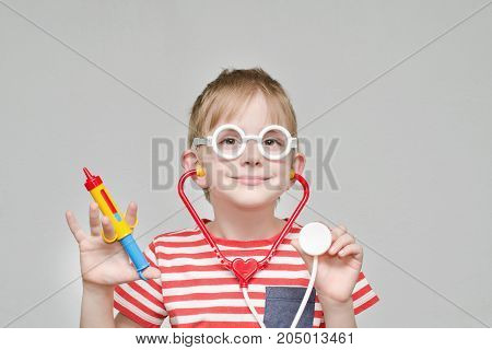 Cute Boy Playing Doctor. Toy Syringe, Glasses And Phonendoscope. Portrait
